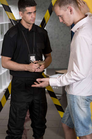 csi: Policeman with a badge and suspect standing in front of a yellow crime scene