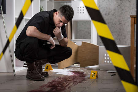 crime scene tape: Young policeman collecting evidence standing behhind yellow crime scene tape