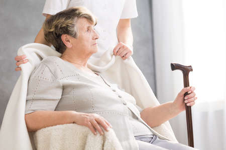 homecare: Senior woman with a walking stick and her carer