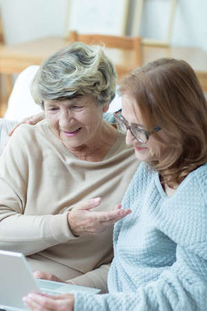 use computer: Female caregiver learning older woman hot to use computer Stock Photo