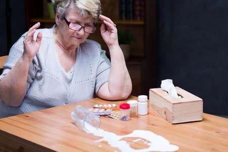 beside table: Sad senior woman sitting beside table, medicines and splash of milk on the table, dark background Stock Photo