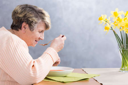 beside table: Senior woman sitting beside table, eating a soup
