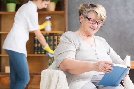 homecare: Senior woman relaxing with book, professional caregiver doing housework Stock Photo