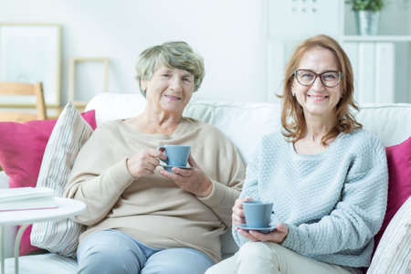 haushaltshilfe: Aged smiling carer and sick older woman drinking tea together Lizenzfreie Bilder