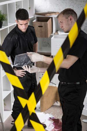 crime scene tape: Two policemen standing behind yellow crime scene tape Stock Photo