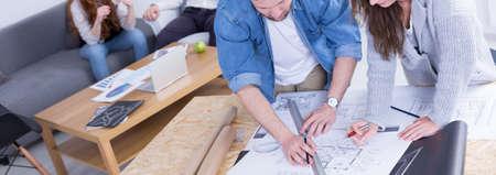 personas reunidas: Dos jóvenes que trabajan juntos en un nuevo proyecto de construcción en la compañía. Apoyado por encima de papel con bosquejo Foto de archivo