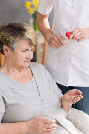 carer: Carer dosing medicines to ill, senior woman