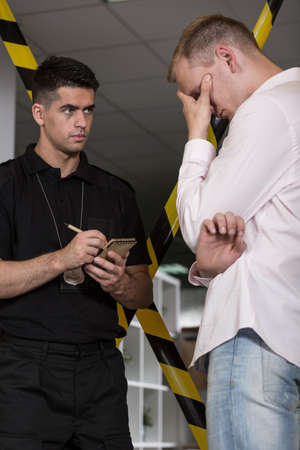 testify: Handsome policeman with a badge doing notes and despair witness