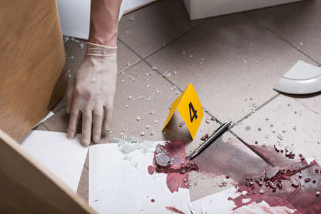 criminal investigation: Close up of a bloody splash, hand in a white glove