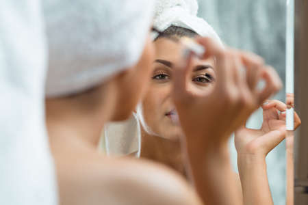 light complexion: Shot of a young beautiful woman using a mascara and wearing a towel