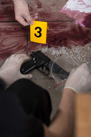 evidence bag: Close up of a policeman holding a gun and an evidence bag Stock Photo