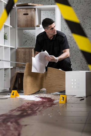 csi: Policeman during work standing behind yellow crime scene tape Stock Photo