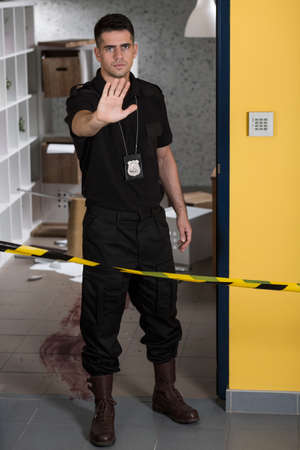 csi: Policeman holding hand in a stop gesture behind yellow crime scene tape