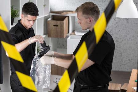 evidence bag: Policemen in white gloves during work, holding gun and evidence bag