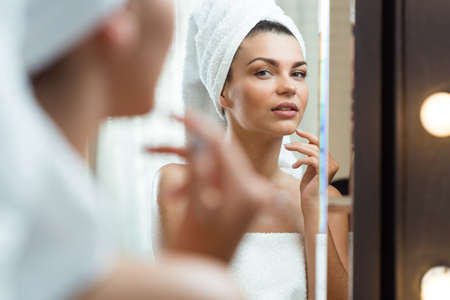 bathroom women: Shot of a young woman with a towel wrapped on her head Stock Photo