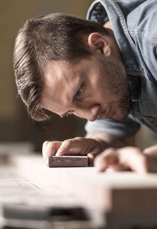 muebles de madera: Primer plano de hombre joven y enfoque de trabajo en la carpintería de muebles de madera nuevos