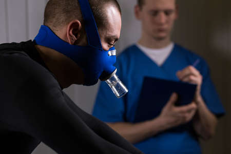 a medical examination: Sportsman in a respiratory mask is exercising while the doctor is writing down the results Stock Photo