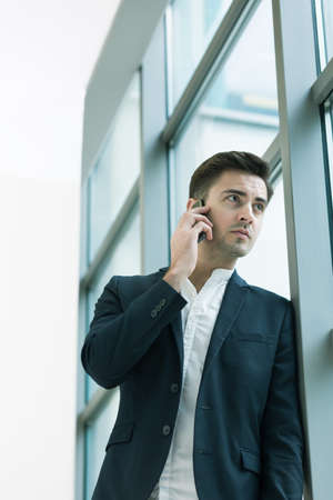 graduation suit: Young handsome businessman in suit talking on the phone about business cases