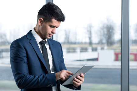 man business oriented: Concentrated, smartly dressed man using a tablet