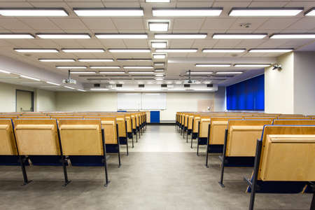 shot from behind: Shot from behind of a lecture hall towards whiteboard