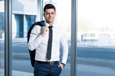 glass wall: Smiling young man dressed smart casual standing by a glass wall Stock Photo