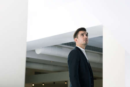 graduation suit: Young elegant student in new modern college building. Looking on the ceiling Stock Photo