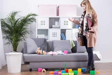 mess: Young tired mother coming back home from work. On the floor childrens toys in mess