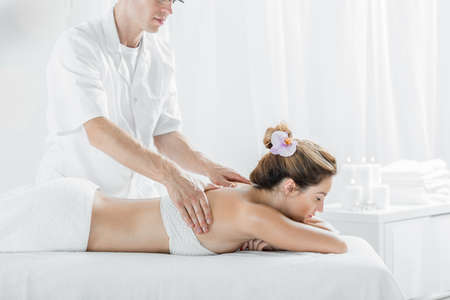 therapeutic massage: Young woman having professional therapeutic massage, light interior