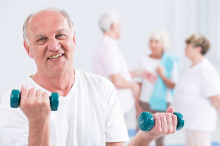 age old: Portrait of a smiling elderly man doing a biceps curl with two weights, with his friends in the blurry background