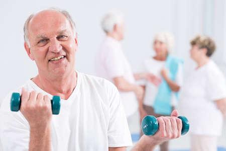 vecchiaia: Ritratto di un uomo anziano sorridente facendo un ricciolo bicipiti con due pesi, con i suoi amici sullo sfondo sfocato