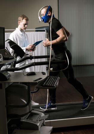 sportsman: Doctor is supervising sportsman on a treadmill