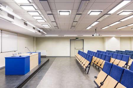 azul marino: sala de conferencias con escritorio y filas de asientos, con elementos de color azul marino