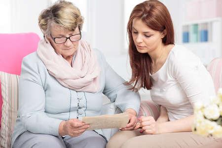 Grootmoeder en kleindochter zitten samen op een bank in een gezellig interieur
