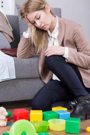 agotado: Mujer bastante joven cansada que tiene funciones después del trabajo. Sentado exhausto en el suelo y apoyándose en un sofá Foto de archivo