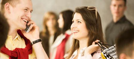 multitud gente: hombre feliz hablando por teléfono celular, sonriente mujer con bolsas de la compra, multitud de personas en el fondo