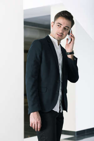 alumnus: Handsome young confident businessman talking the phone on his modern college Stock Photo