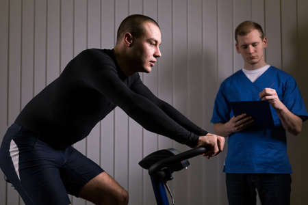 cardiovascular workout: Sportsman is sitting o a stationary bike and the doctor is supervising him