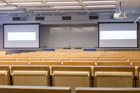 lecture theatre: Lecture hall with projection screens and shaded light