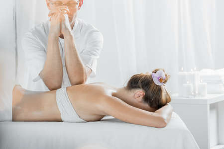 therapeutic massage: Masseur and woman lying in light interior during therapeutic massage