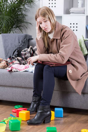mess: Pretty young woman having a headache after hard day at work. All around her mess by kids toys