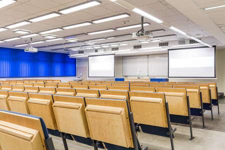 sala de conferencias con ventanas sombreadas y pantallas de proyección Foto de archivo