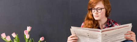 periodicos: Primer plano panorama de una mujer joven, de pelo rojo que lee un periódico junto a un muro negro y ramo de tulipanes