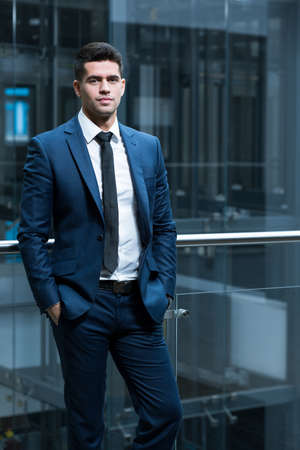smartly: Young, smartly dressed man in an office building, leaning against a metal and glass rail Stock Photo