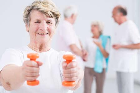 persona mayor: Retrato de una anciana enérgica ejercicio con pesas, con sus amigos en el fondo borroso