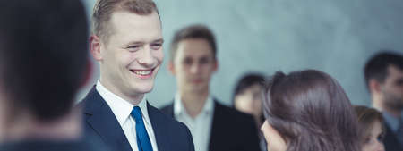crowd: Smiling man in elegant suit talking with woman, standing in crowd of people, panorama