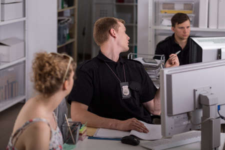 police station: Show of two policemen and a young woman at a police station Stock Photo
