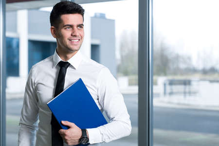 navy blue: Smiling young man in a white shirt and a tie, holding a navy blue folder Stock Photo