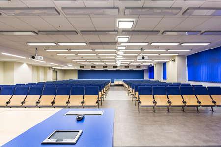 Collegezaal met marineblauwe gegevens gezien van achter het bureau