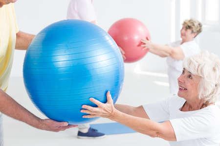 persona mayor: Primer plano de una señora mayor alegre que pasa una bola azul del ejercicio a su compañero de acondicionamiento Foto de archivo
