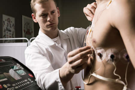 cardiovascular workout: Doctor is putting an electrode on a chest of sportsman
